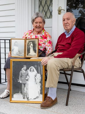 Mae and George Ryan, both 98, of Milton, hold a framed photo taken of them leaving St. Gregory's Parish in Dorchester on their wedding day Aug. 29, 1945. Their son, George Thomas Ryan, of Orleans, is in the photo on the upper left.  Wednesday, August 26. (Mike Mejia/For The Patriot Ledger).