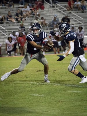 Effingham County quarterback Zach Garcia looks to hand off to running back Josh Thrift during the Rebels' 21-13 season-opening victory over Grovetown on Sept. 4.