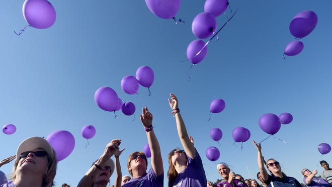 """Crystal Strous, third from left, the mother of Amanda Strous, joins a crowd on the center of the field hockey field at Dallastown Area High School to release balloons in honor of her daughter. Amanda, who played field hockey at Dallastown, """"was truly amazing,"""" her father said. Amanda was murdered in North Carolina in June."""