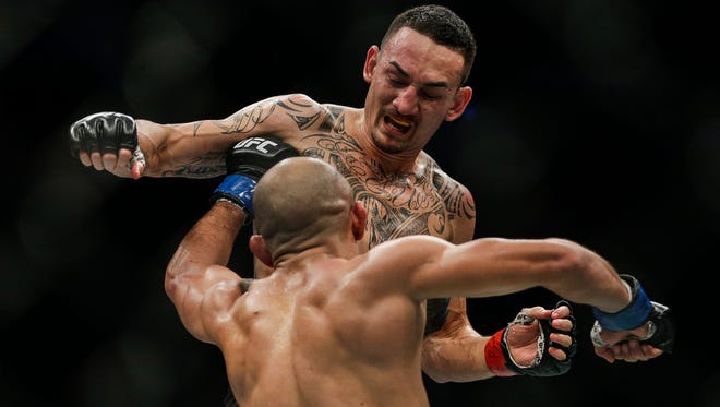 Max Holloway, above, jumps for a dive punch against Jose Aldo during the UFC 218 Featherweight championship at the Little Caesars Arena in Detroit, Saturday, Dec. 2, 2017.