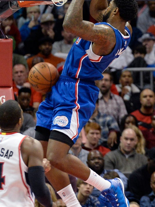 Los Angeles Clippers center DeAndre Jordan, right, dunks against the Atlanta Hawks during the first half of an NBA basketball game, Tuesday, Dec. 23, 2014, in Atlanta. (AP Photo/John Amis)