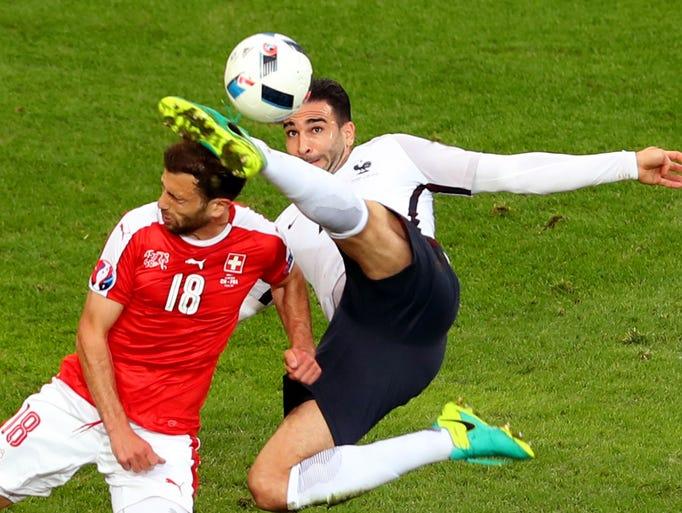 France's Adil Rami kicks the head of Switzerland's
