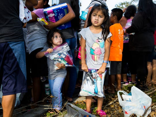 Families wait for donated supplies to be handed out