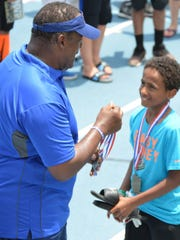 Former NFL coach Ray Sherman awards Port Huron's De'Christopher Green with the Offense-Defense Camp MVP.