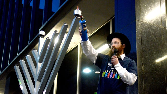 Rabbi Mendel Cunin, of Chabad of Northern Nevada, lights the giant menorah on Sunday at Reno City Hall in celebration of the Jewish holiday Hanukkah.