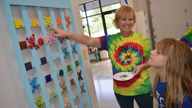 Mo'sArt owner Missy Tanner assists young artist Katelyn Kirtley, 10, of Brandon with her paint selection.