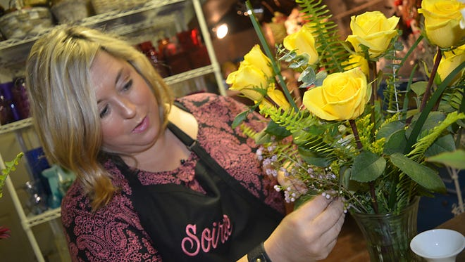 Soiree Gifts and Floral is now open at its new location at 601 Northbay Drive in Madison. Owner Rebecca Norma Carroll Harrison uses fresh yellow roses, spray roses, pink wax flowers, eucalyptus and Boston fern in the floral arrangement she is preparing for a new customer.