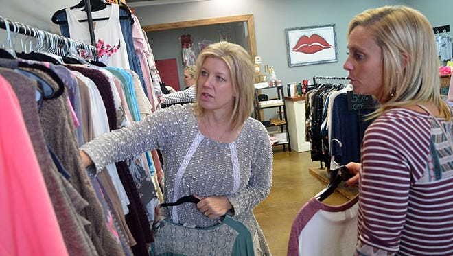 Red Wagon Boutique owner Deanna Abernathy, center, assists customer Jessica Sanford with her selection of clothing.