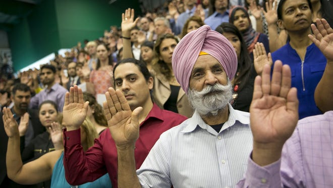 Guillermo Leal, left, of Mexico, and Mohinder Singh, of India, take the oath of citizenship at a naturalization ceremony in Austin, Texas, on June 29, 2017.