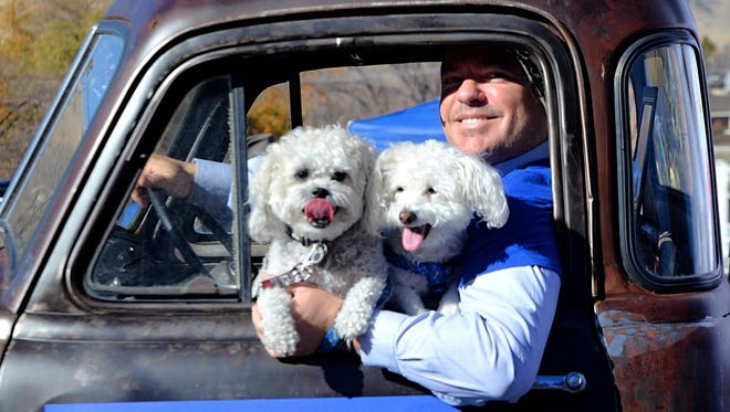 A man holds two dogs as he peers from out of a window while driving a pickup truck during the 79th Annual Nevada Day Parade on Oct. 28, 2017 in Carson City.