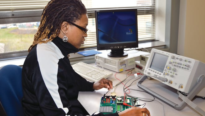 MATC graduate Serita Campbell works on a circuit board in an electronics class. She is now a manufacturing technician at GE Healthcare.