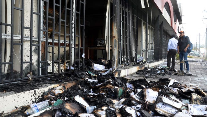 Burnt documents lie outside of the state comptroller's building after protesters torched the building in the state capital city of Chilpancingo, Mexico, on Nov. 12, 2014. Violent protests over the disappearance of 43 college students continue and are now threatening tourism in the nearby resort city of Acapulco ahead of a major holiday weekend.