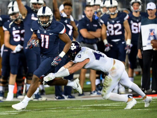 Connecticut running back Arkeel Newsome (22) gains yardage in the fourth quarter of an NCAA college football game against Holy Cross, Thursday, Aug. 31, 2017, in East Hartford, Conn. (AP Photo/Stephen Dunn)