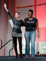 Rose McGowan, left, waves after being introduced by Tarana Burke, right, founder, #MeToo Campaign. McGowan recently went public with her allegation that film company co-founder Harvey Weinstein raped her.