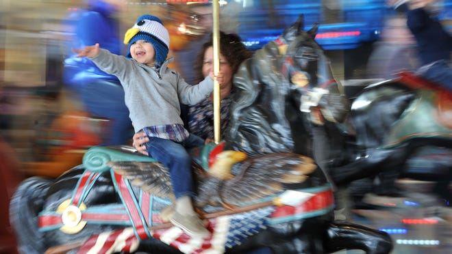 "Elias Long, 2, waves to his dad while taking a spin on the landmark Richland Carrousel Park. Such attractions are among the area's strengths. For more information, see our Business Journal special ""Blueprint"" section, inside today's edition."
