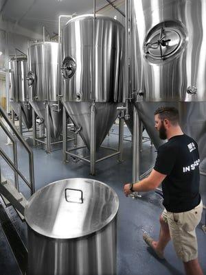 Jonathan Pacha walks past large fermenters inside Proof Brewing Company.
