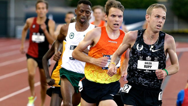 Galen Rupp, right, leads the pack on his way to winning the men's 10,000 meters at the U.S. Track and Field Championships in Eugene, Ore., Thursday, June 25, 2015.