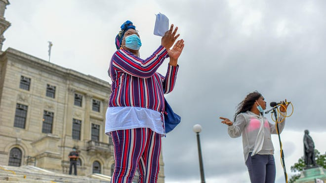 Terri Hodge of Direct Action for Rights & Equality applauds speaker Jesse Andrews on the State House steps Friday at a rally in support of those incarcerated in Rhode Island.