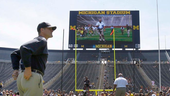Michigan head coach Jim Harbaugh oversees the  introduction of the team's players by position group to the fans during football media day on Thursday, August 6, 2015, in Ann Arbor.