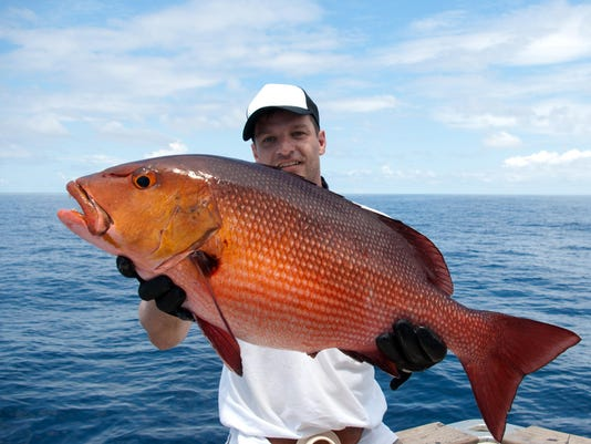 Man near the lake holding a large red snapper