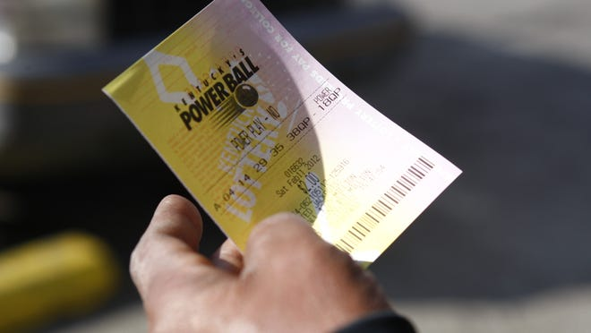 Jesse Shobe holds his $2 Powerball ticket after purchasing it at Shorty's on Dixie Highway Saturday afternoon.  (By Matt Stone, The Courier-Journal) Feb. 11, 2012