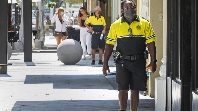 Private security guards patrol Clematis Street Monday in downtown West Palm Beach.
