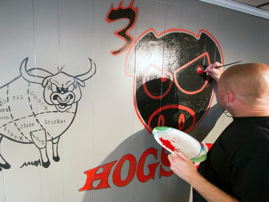 Eric Klunk, a tattoo artist with Skin Images in Hanover, creates a wall mural at 3 Hogs BBQ in Spring Grove.