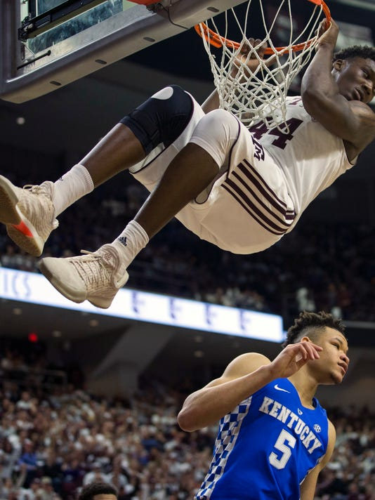 Texas A&M forward Robert Williams (44) hangs from the rim after dunking over Kentucky forward Kevin Knox (5) during the first half of an NCAA college basketball game Saturday, Feb. 10, 2018, in College Station, Texas. (AP Photo/Sam Craft)