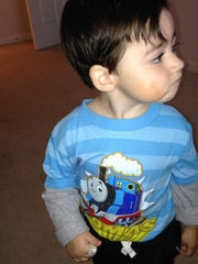 "My 2-year-old son Dylan, wearing a blue Thomas the Tank Engine shirt, after ""applying"" a few dabs of concealer and borrowing my sparkly silver ring."