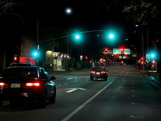 Cars travel along Pine Street Monday night in Redding.