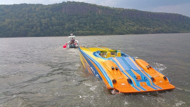 The Westchester County Marine Unit tows a catamaran after the power boat operator led police boats on a chase that reached 100 mph on the Hudson River from the Tappan Zee Bridge to Yonkers Sunday.