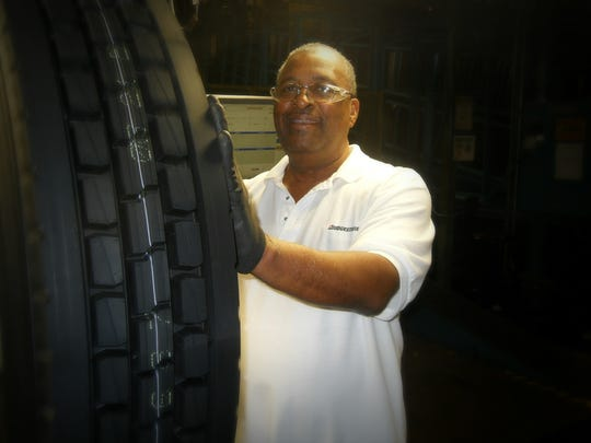 Fletcher Gray checks a newly pressed radial tire at Bridgestone's manufacturing plant in La Vergne.