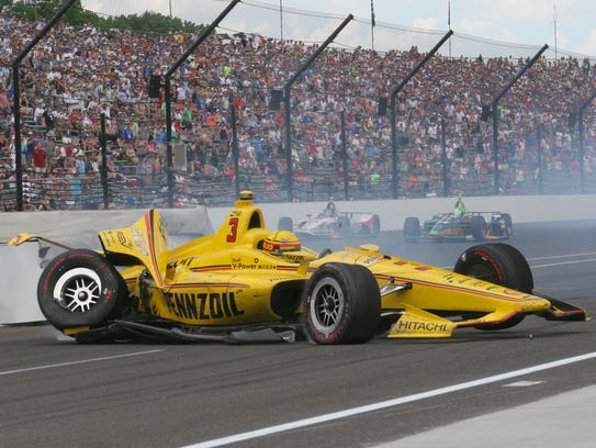 Helio Castroneves slides into the pit area after spinning off the fourth turn and hitting the wall Sunday.