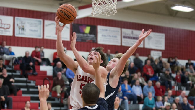 Lenape's Jake Topolski drives to the basket between a pair of Shawnee defenders in the fourth quarter of Tuesday's Olympic Conference showdown.