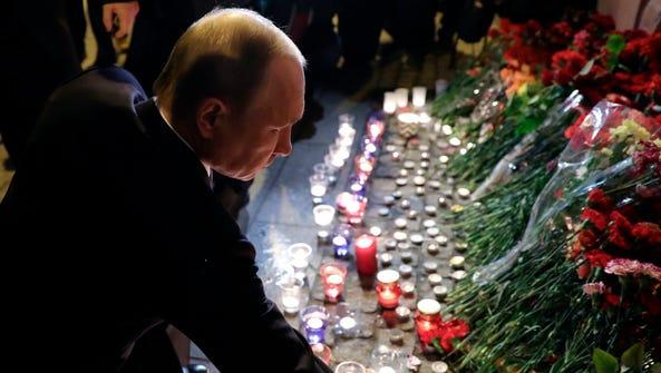 Russian President Vladimir Putin places flowers near