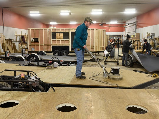 A sander is used to smooth out joints in the floors of new fish houses Tuesday, Feb. 16, at the Ice Castle Fish Houses production facility in Montevideo.