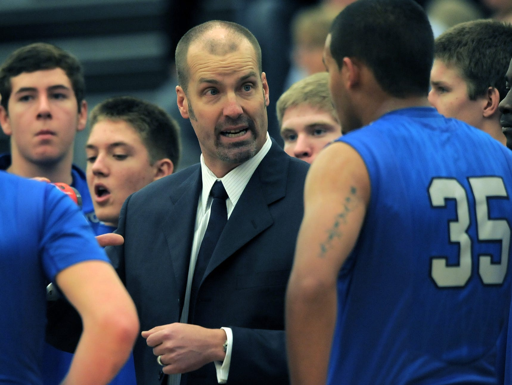 Poudre coach Steve Hawes confers with players during the game against Fossil Ridge at Fossil Ridge High School on December 18, 2012.