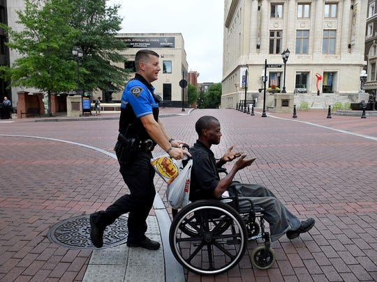 Officer Nate Phillips helps Brian Livingston up a Main Street hill while patrolling downtown Greenville on foot Thursday.