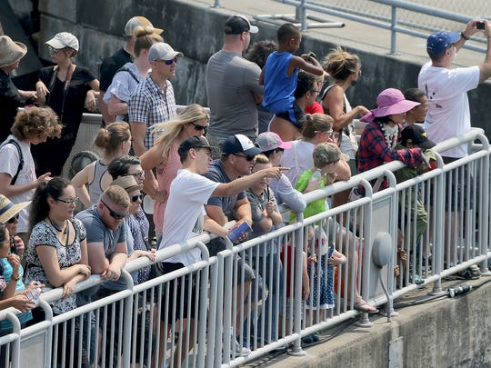 Spectators line up on a hot and hazy afternoon to watch the Seafair Fleet Week parade of ships from Pier 66.