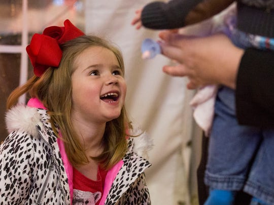 Maddie Crowe, 5, laughs with her mom as she waits her turn to meet Santa at the West Side Nut Club's annual Santa Land on Sunday afternoon.