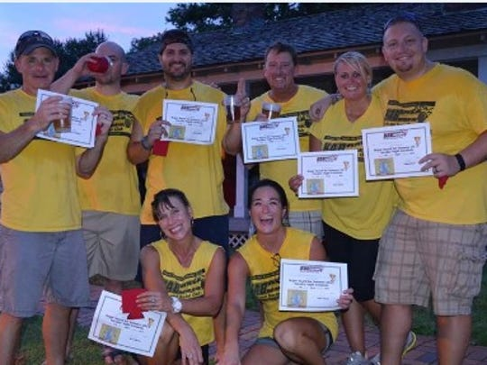 The Cornholioers show off their certificates after being named the Summer 2015 League Champions. Michelle Collins is kneeling on the right, with her husband, Mike, directly behind her. The Collinses met while playing corn hole and were married last March.