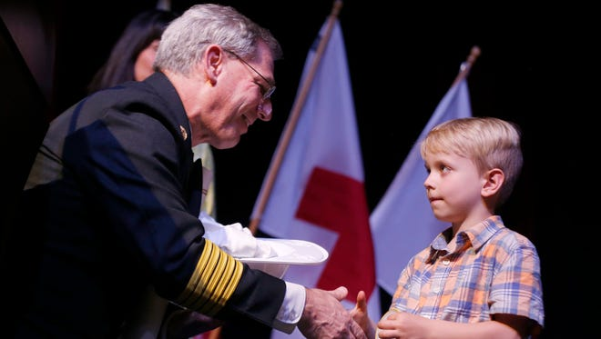 Springfield Fire Chief David Hall shakes hands with 5-year-old Graham Lampe after naming him an honorary firefighter for the day during the American Red Cross Everyday Heroes event on Wednesday. Graham was being honored for calling 911 to save his grandmother.