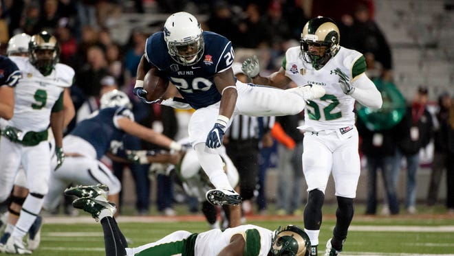 Wolf Pack running back James Butler jumps over Colorado State safety Trent Matthews during the 2015 Arizona Bowl.