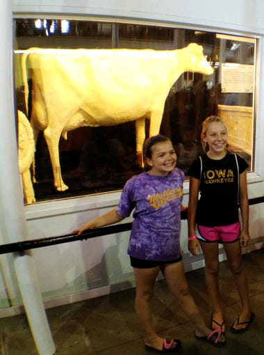 John Gabriel, of Muscatine, photographs his daughter Sophie Gabriel, 10 and her friend Hallie Hanssen, 10 of Muscatine in front of the butter cow Monday afternoon, Aug. 7, 2013 at the Iowa State Fair. This is a popular tradition for many fairgoers.