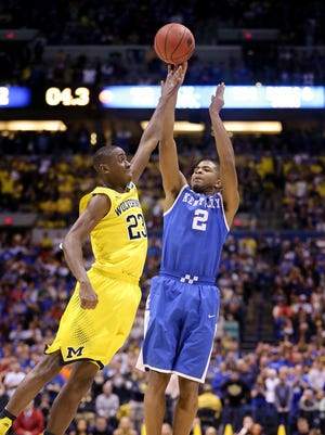 Kentucky's Aaron Harrison shoots the game winning three-pointer over Michigan's Caris LeVert with seconds to go in the game.