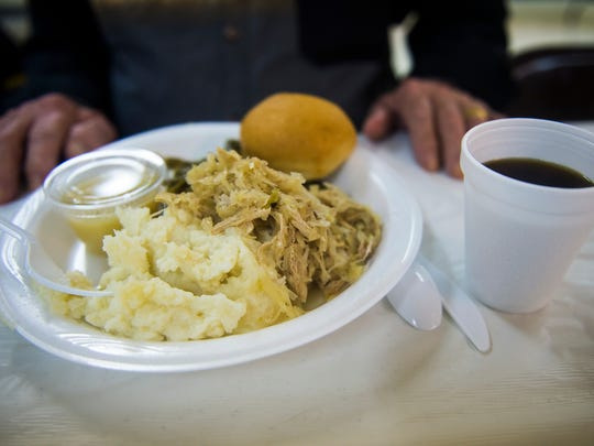 A diner's plate includes pork and sauerkraut, mashed potatoes, green beans, applesauce, a roll and coffee during the Greenmount Fire Company dinner buffet on Jan. 1, 2016 in Freedom Township.