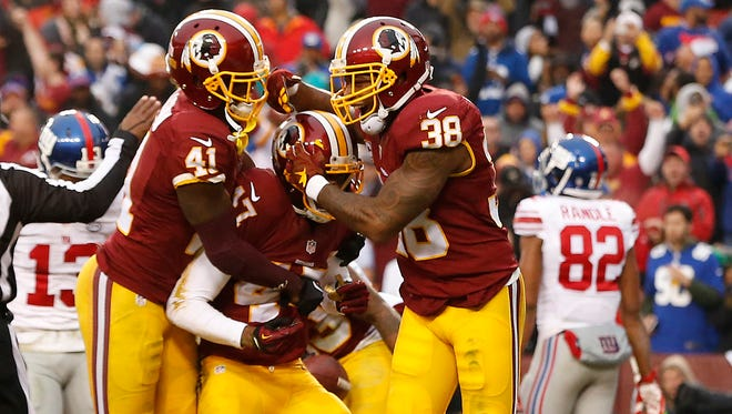 Washington Redskins cornerback Quinton Dunbar (47) celebrates with Redskins free safety Dashon Goldson (38) and Redskins cornerback Will Blackmon (41) after intercepting a pass in the end zone against the New York Giants in the third quarter at FedEx Field.