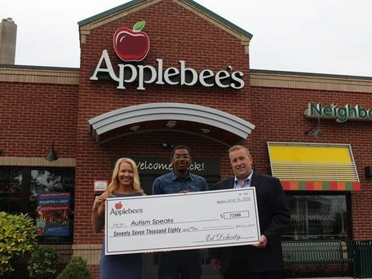 """Representatives of Applebee's Neighborhood Grill & Bar on June 16 present a check for $77,080 to Autism Speaks, whose mission is to change the future for all who struggle with an autism spectrum disorder. In support of Autism Awareness Month, Applebee's locations owned and operated by Doherty Enterprises in New Jersey, Long Island, Florida and Georgia donated a portion of the proceeds from the sale of """"blue"""" drinks, as well as paper puzzle pieces, throughout April. Applebee's locations in New Jersey raised a total of $28,293, which includes matching donations from Skyy Vodka and Miller Coors, as well as the proceeds from flapjack fundraisers held at its Flemington, Hillsborough, Manchester, Parsippany, Tinton Falls, Toms River and Woodbridge restaurants. From left: Anne Juaire, director of corporate development, Autism Speaks; Jerome Fleming Jr., bar server, Applebee's; and Kurt Pahlitzsch, director of operations, Applebee's."""