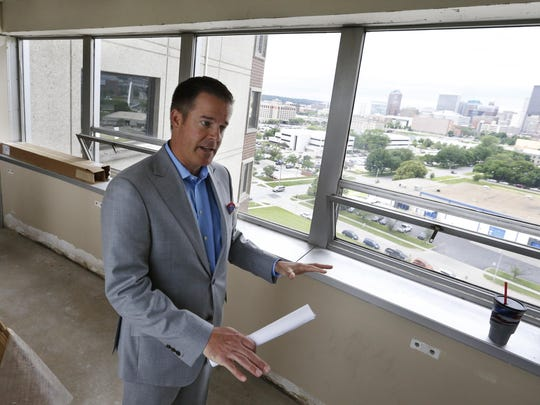 Troy Strawhecker talks about the work being Tuesday as he stands in one of the walkways between the two towers. The former senior living facility on the edge of the East Village is being converted into a market-rate apartment building called The Lyon.