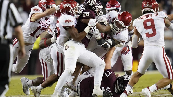 Texas A&M running back Isaiah Spiller is met at the line of scrimmage by the Arkansas defense for a loss Oct. 31 in College Station, Texas.